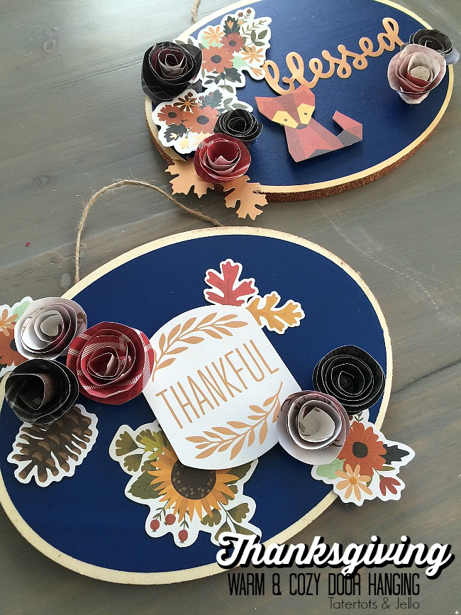 thanksgiving-warm-and-cozy-door-hanging-easy-diy. Easy Thanksgiving Door Hanging. Make a Door Hanging with an inexpensive wood slice, paper and embellishments. Find out how easy it is to make and how to make rolled paper flowers!