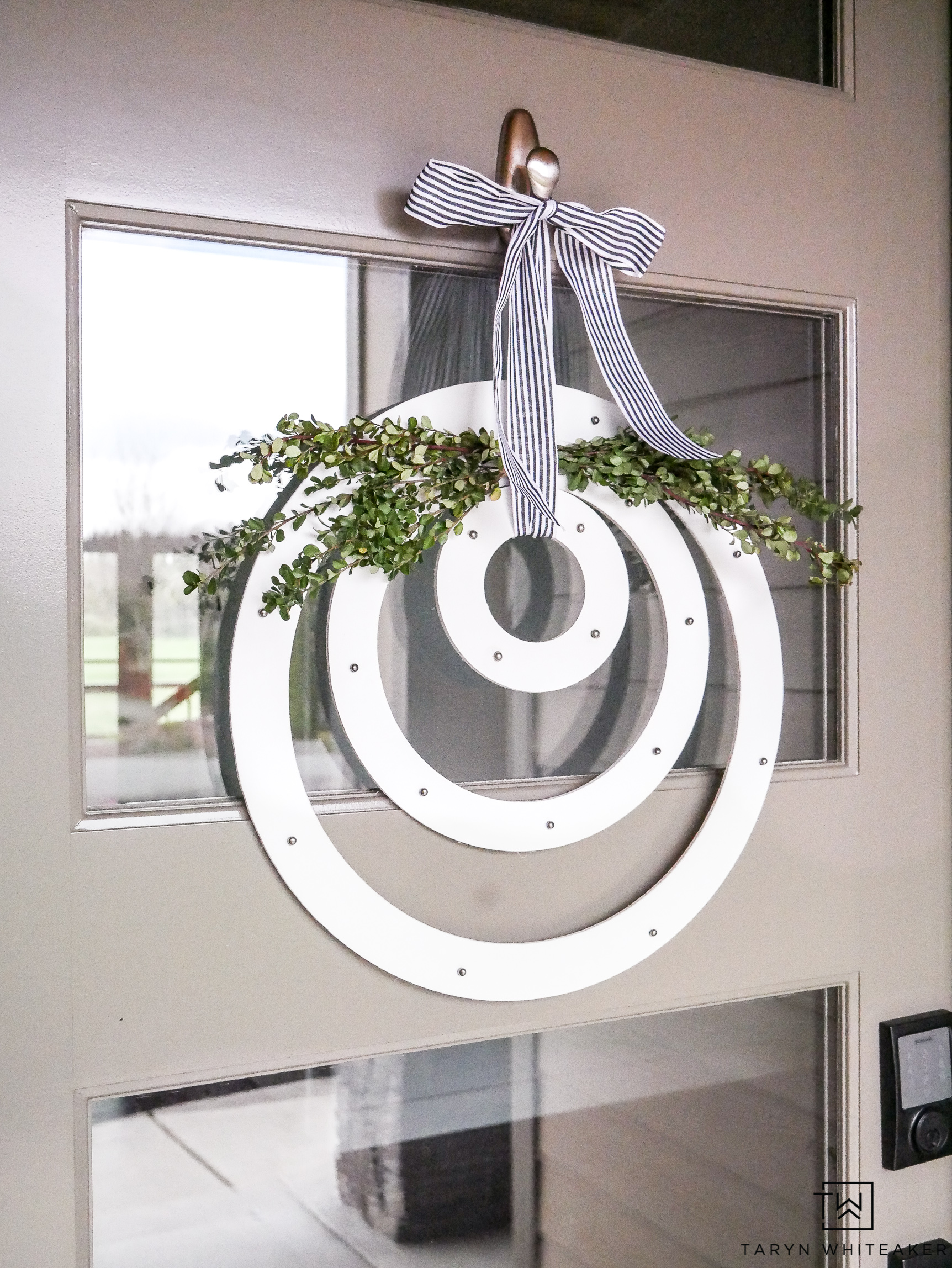 DIY Modern Spring Wreath. Three simple wood circles hung with branches and a striped ribbon hanging on a tan door.