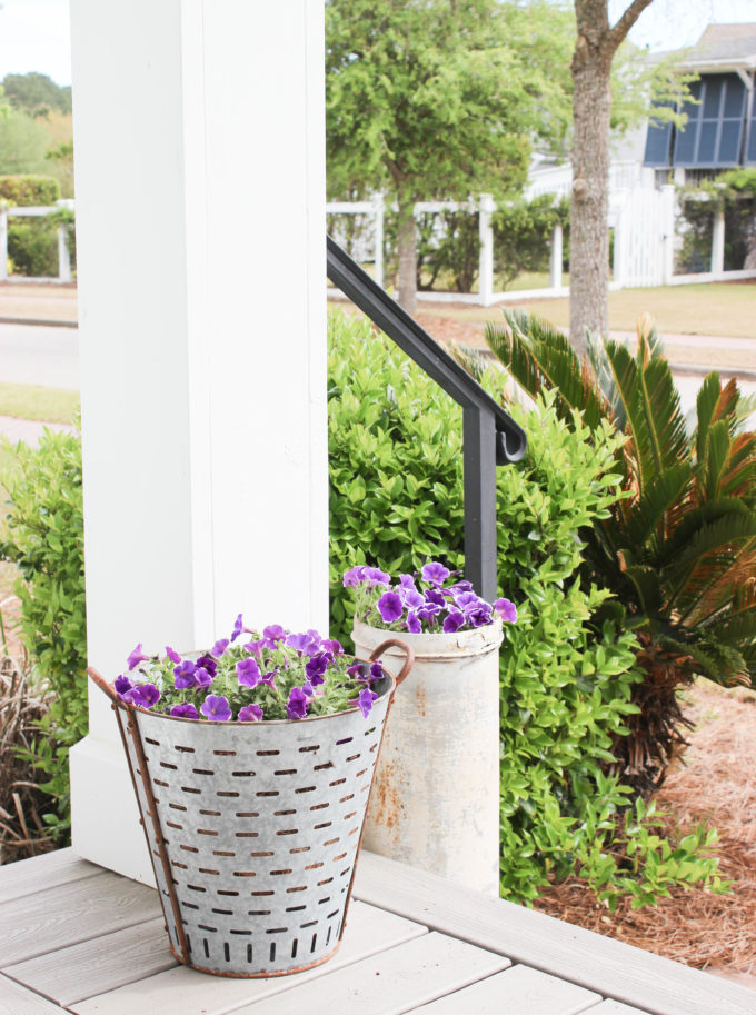 Purple pansies potted in reclaimed metal pots on a porch.