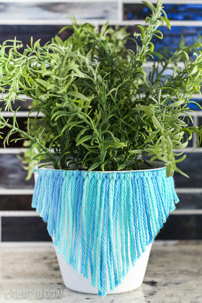 Blue and turquoise yarn wrapped around a white pot and cut into a v shape.