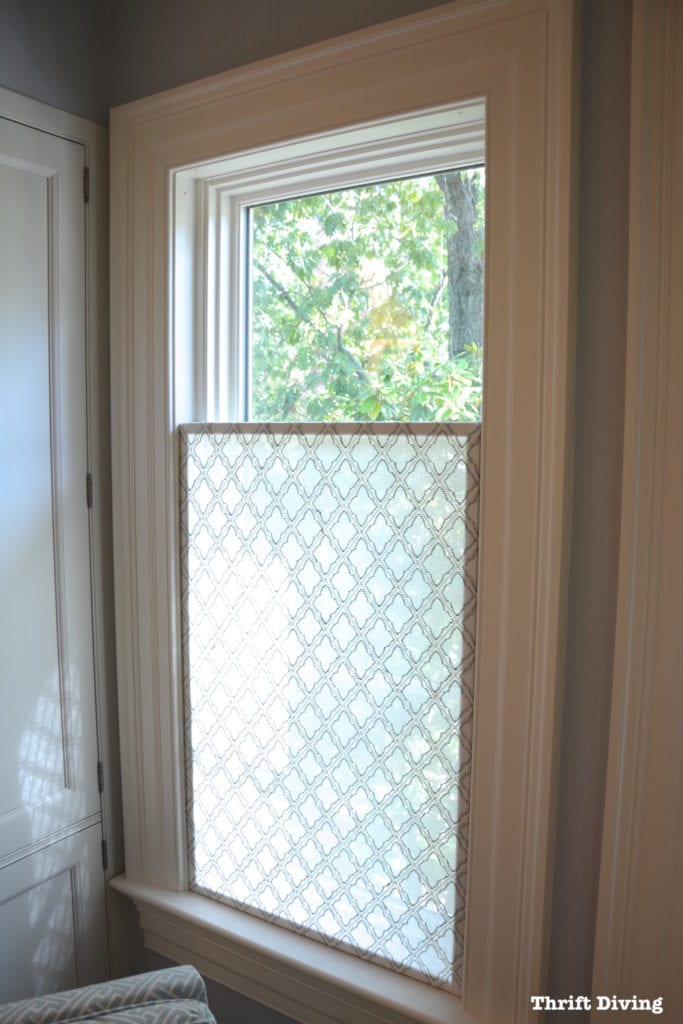 Opaque material wit a trellis patter is hung on the lower half of a window as a privacy screen that still lets light shine through.