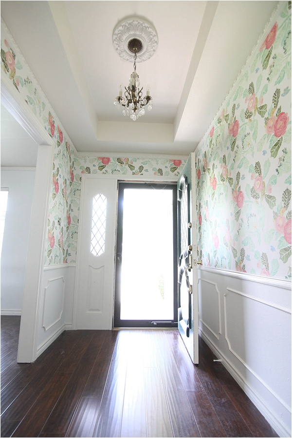 Colorful pink flowers wit hgreen leaves are wallpaper that has been hung on the entryway of a home with white walls.
