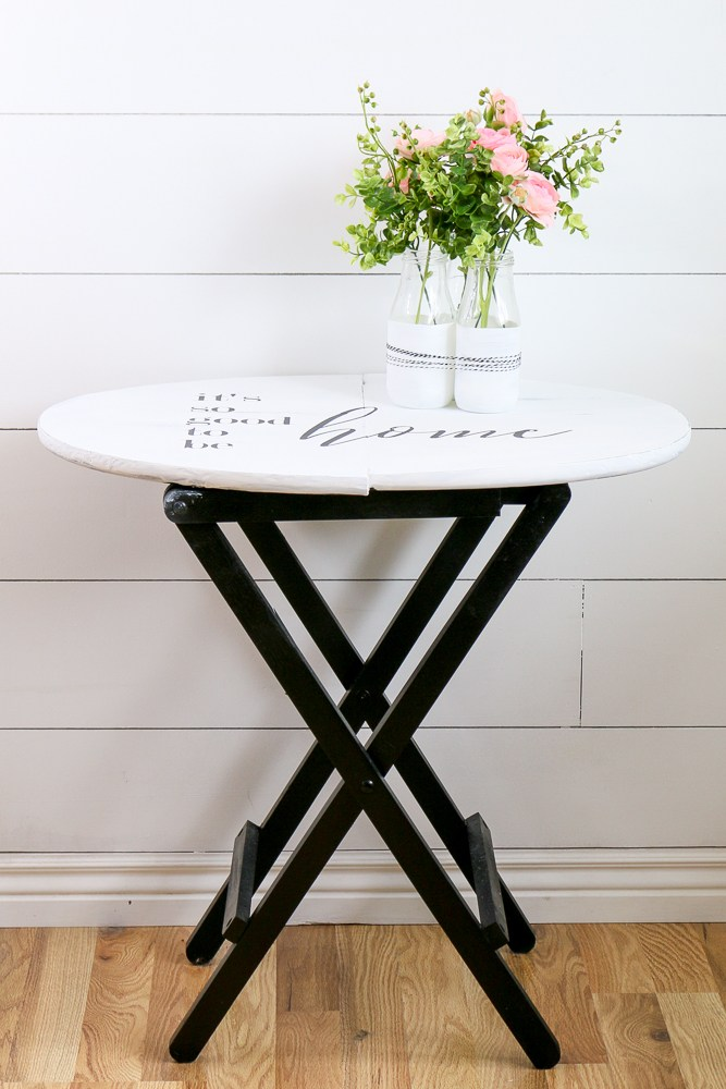 A small foldable bistro table has been painted black at the base and white on top with a saying it's so good to be home stenciled on the top.