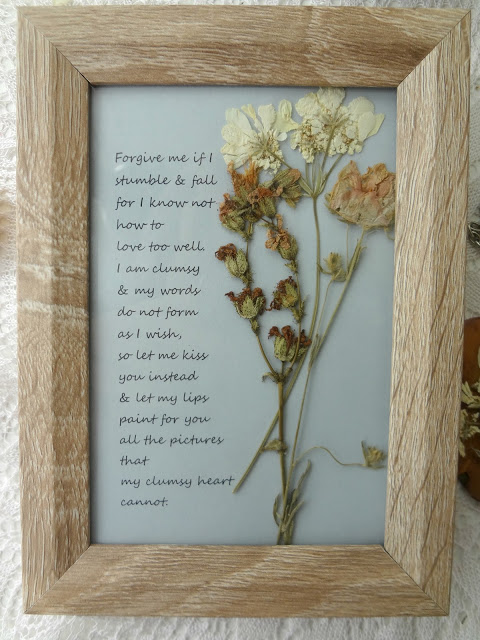 Spring flowers are dried and put inside of a wood frame with a saying written beside them.