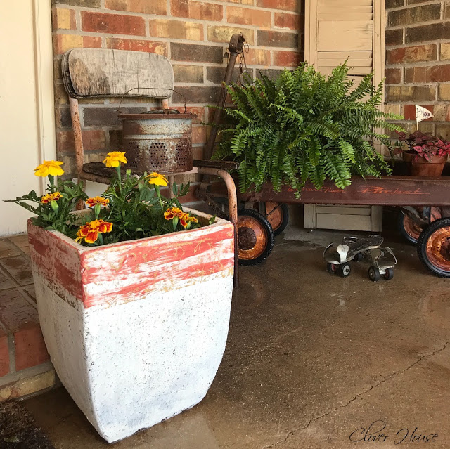 A rectangular container has been painted to look like concrete with orange streaks at the top of the pot.