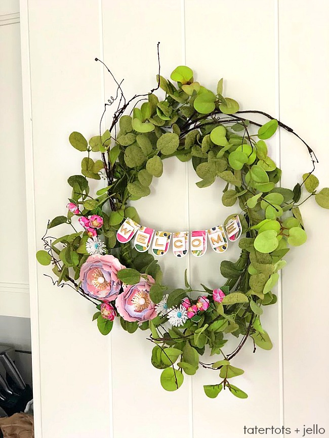 Make a WELCOME Banner Wreath. Combine the beautiful elements of greenery with paper flowers and a paper banner for a wreath that welcomes everyone!