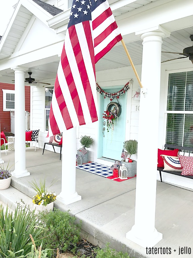 Create a memorable Fourth of July wreath. The galvanized wreath base holds a wooden star surrounded by three flags, a painted 4 and beautiful red and blue flowers and draping greenery.