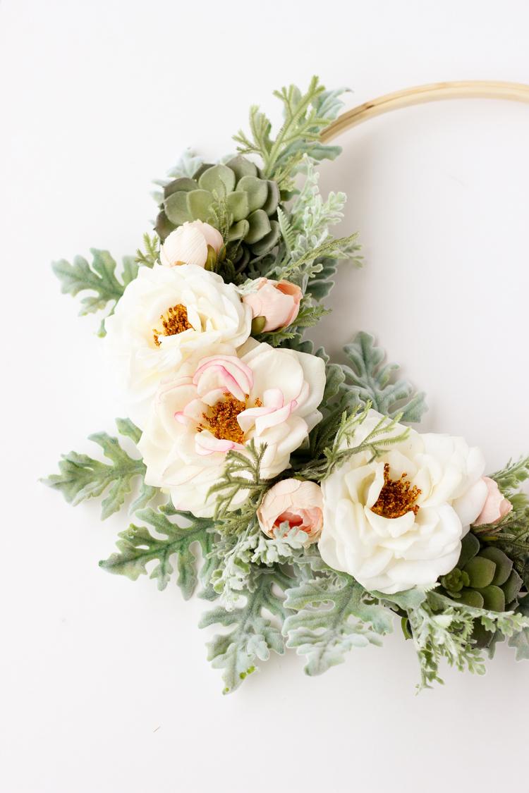 modern metal hoop wreath with white flowers.