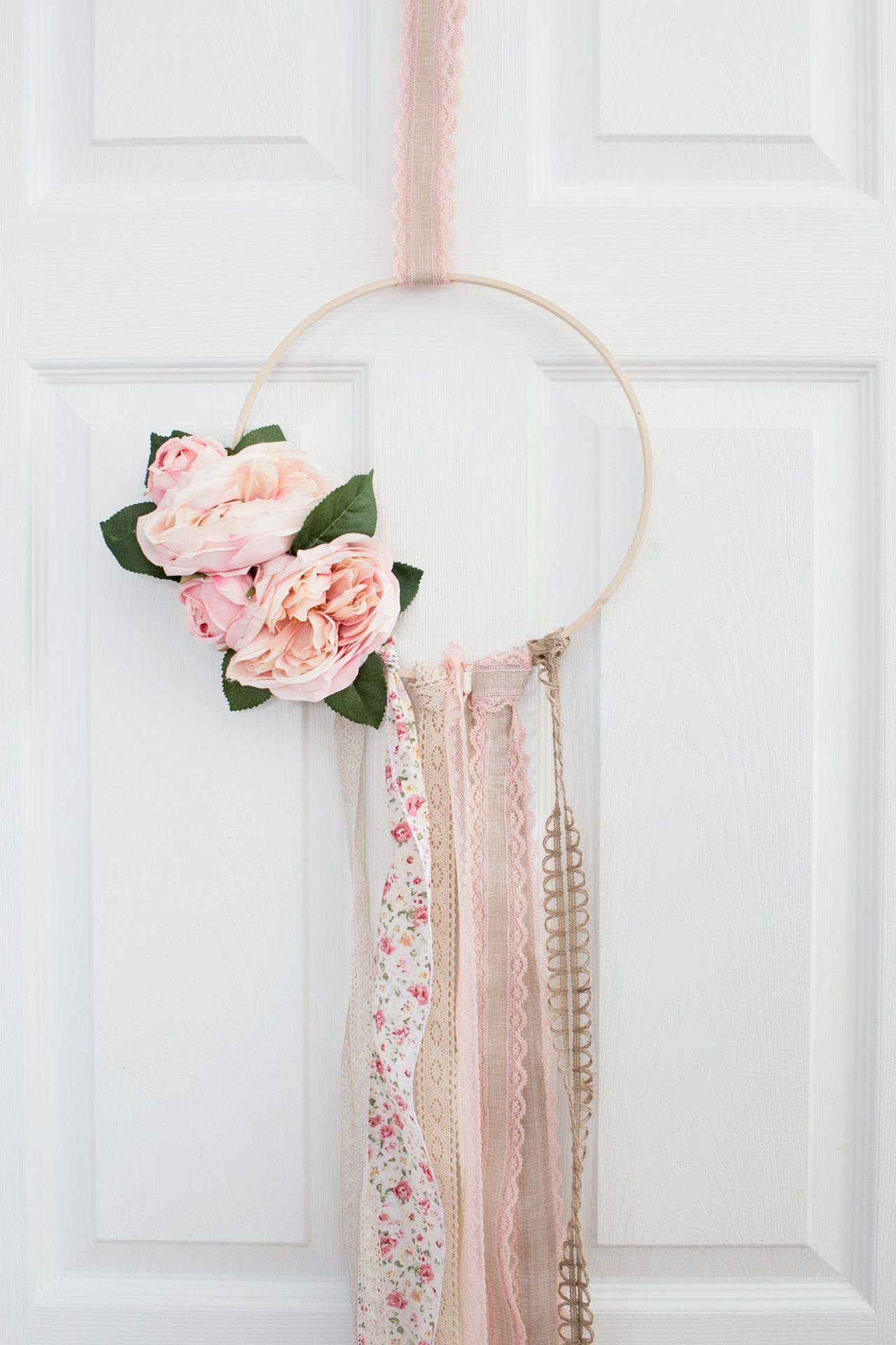 Boho hoop wreath with ribbons nad pink flowers.