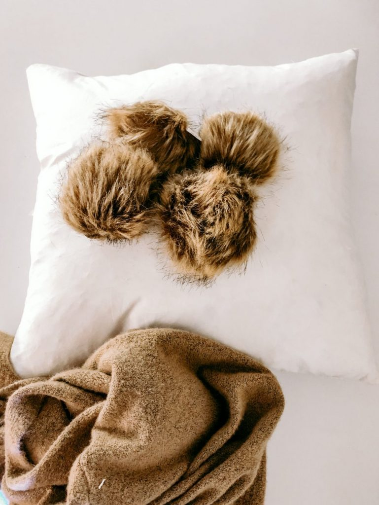 How to make a sweater pillow with fur pom poms.