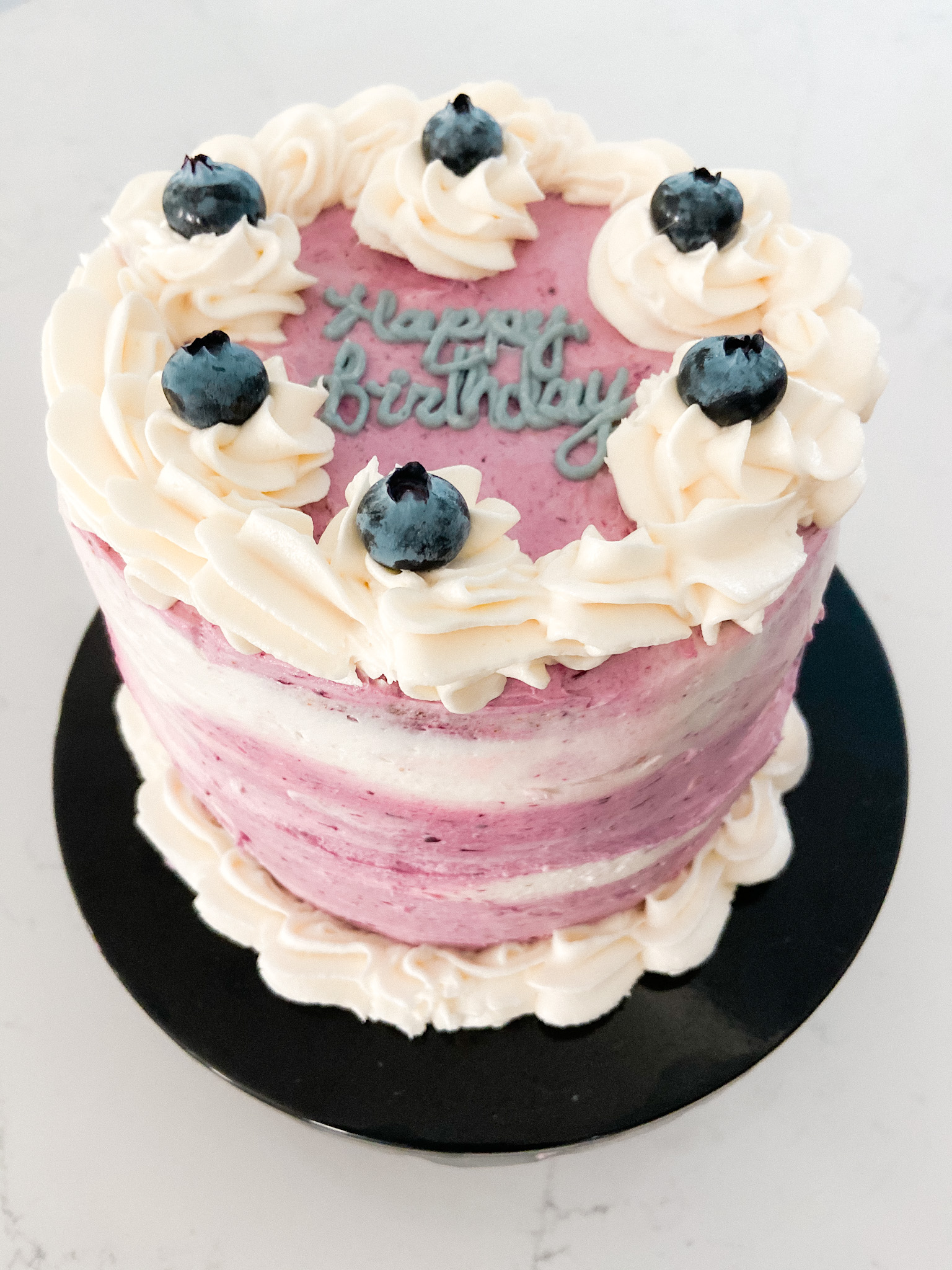 Homemade lemon cake with blueberry frosting and fruit compote filling.