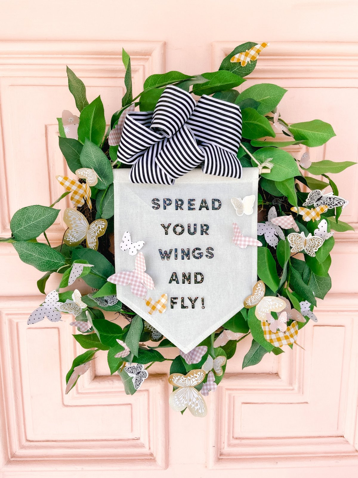 Spring Butterfly Pennant Wreath. Celebrate spring by making this simple wreath with butterflies cut out of cardstock and a big pennant in the middle and a spring saying!