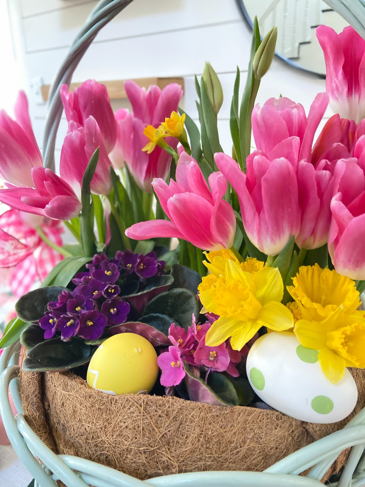 Easter Basket Living Floral Centerpiece. Take an Easter basket, plant flowers inside and cover with a dollar store coir liner for a beautiful spring living centerpiece.
