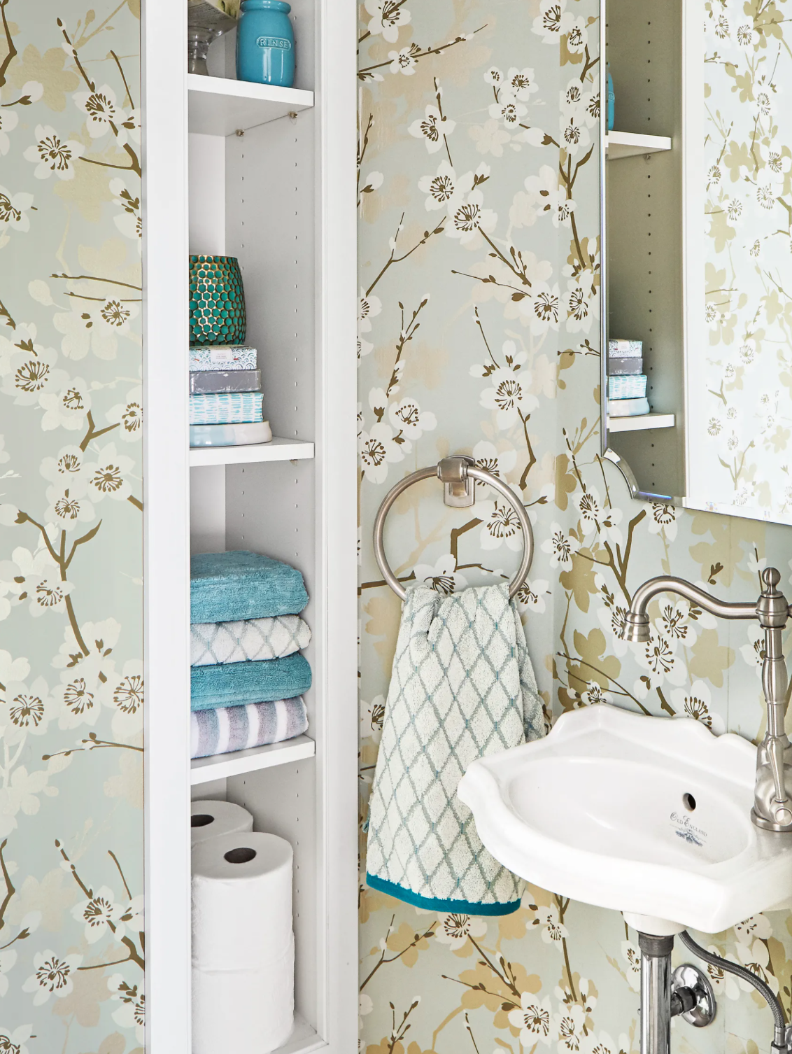 Small Between The Studs Bathroom Niche trimmed with white molding and with floral wallpaper.