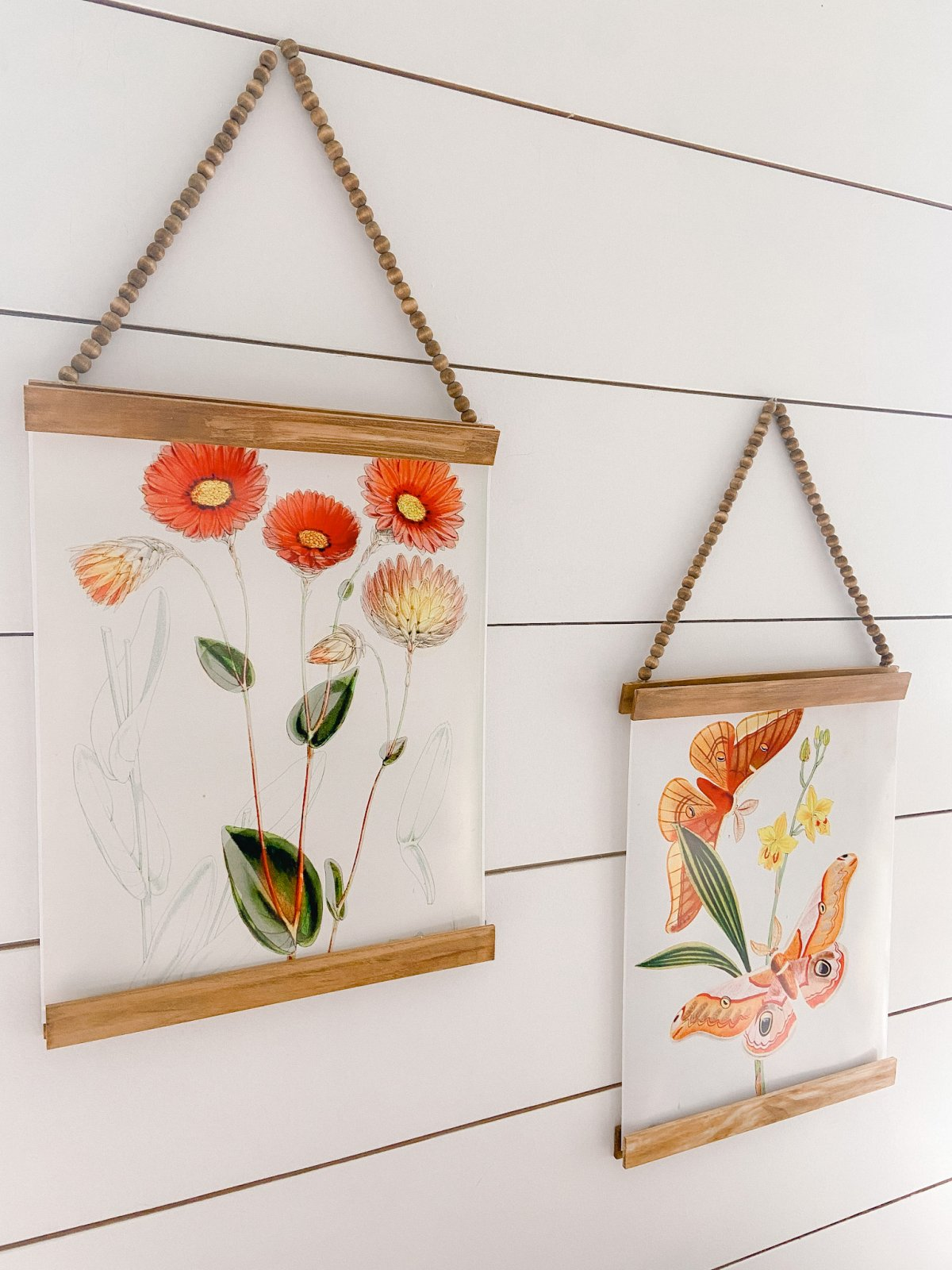 Vintage flowers and butterfly paintings hung on a wall with stained wood strips and beaded string.