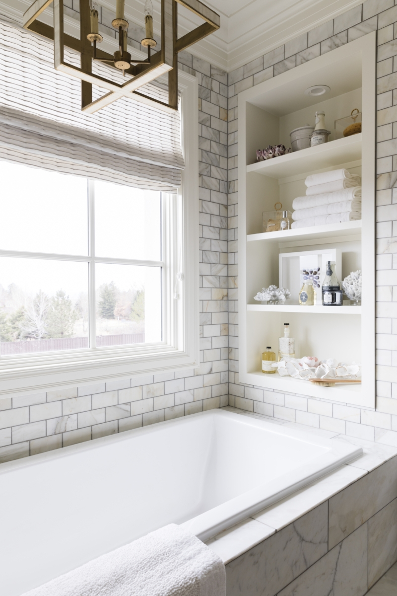 Marble subway tile wall with built in white shelves built in between the studs at the end lf the tub.