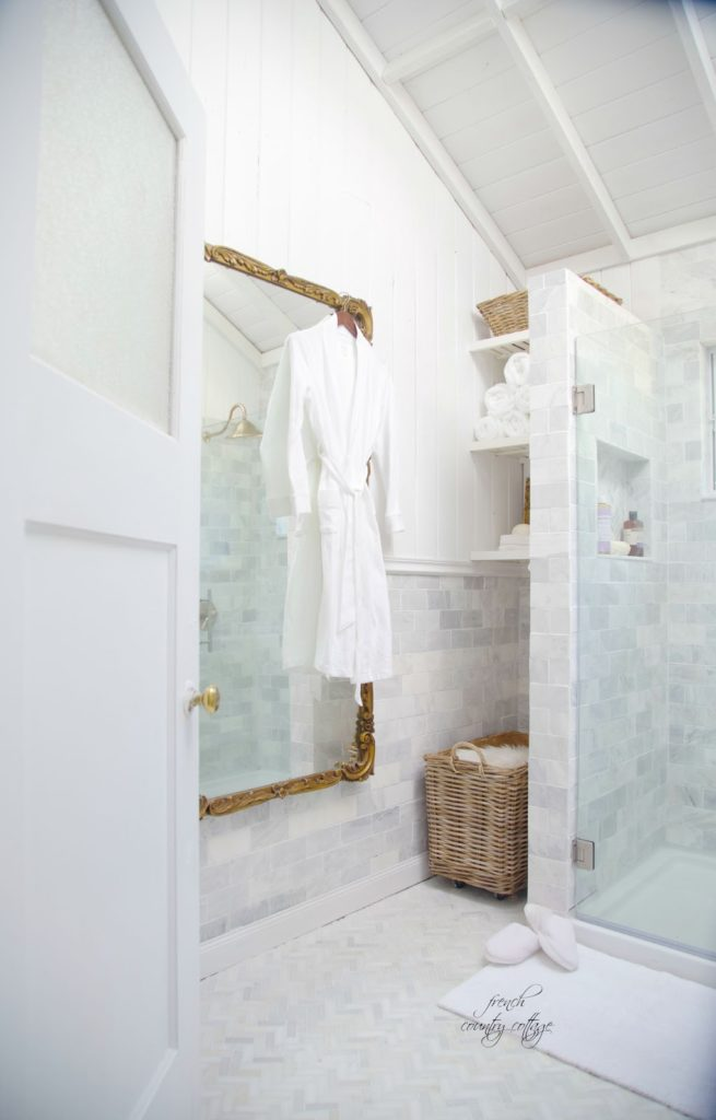 Beautiful marble bathroom remodel with a niche carved out behind the shower for shelves and a laundry hamper.