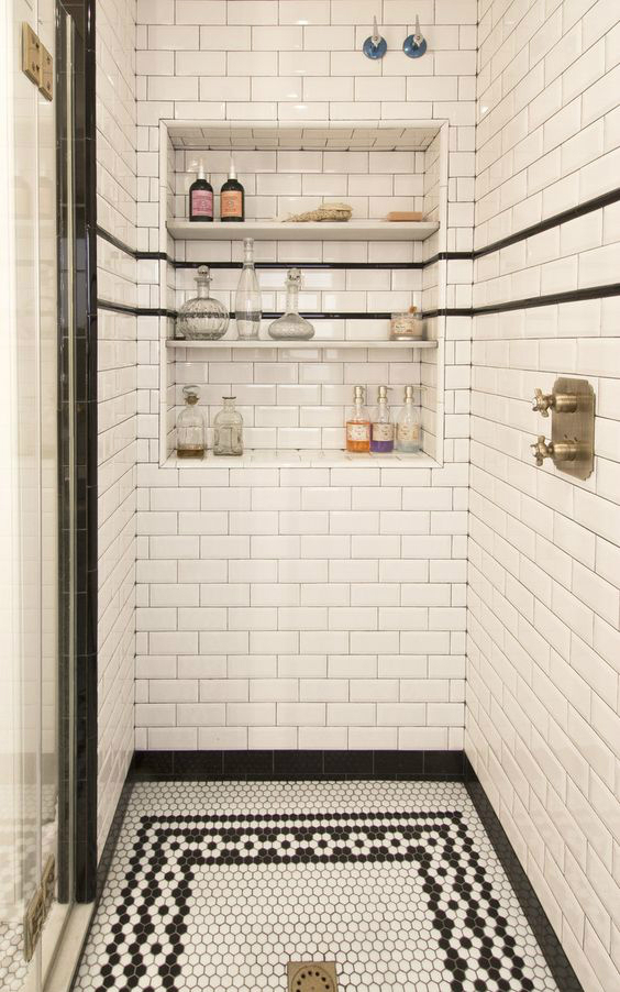 Vintage bathroom remodel with mosaic black and white floor, subway tile surround in the shower and a large niche with three shelves.