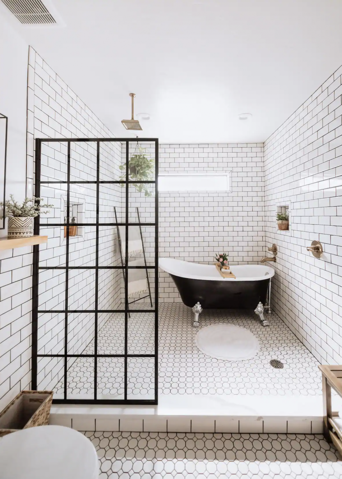 Black clawfoot tub in a shower wet room with subway tile and a glass grid panel.