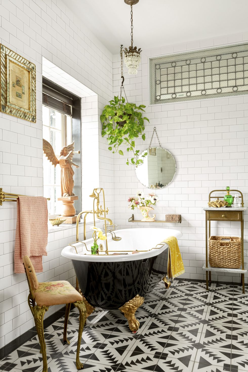 Black clawfoot tub and gold feet against a wall of subway tile and plants.