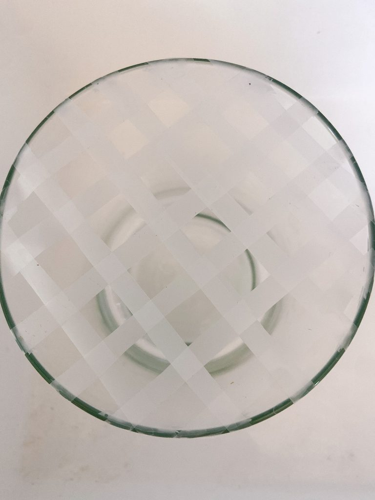 Make a tape grid by cutting tape in half lengthwise and taping the strips in a grid pattern at the top of the vase.