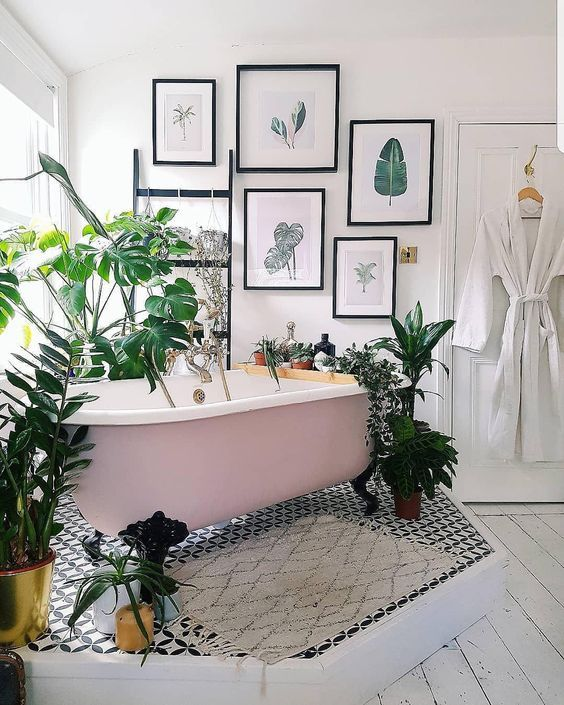 Pink clawfoot tub on a pedestal set at an angle surrounded by plants.