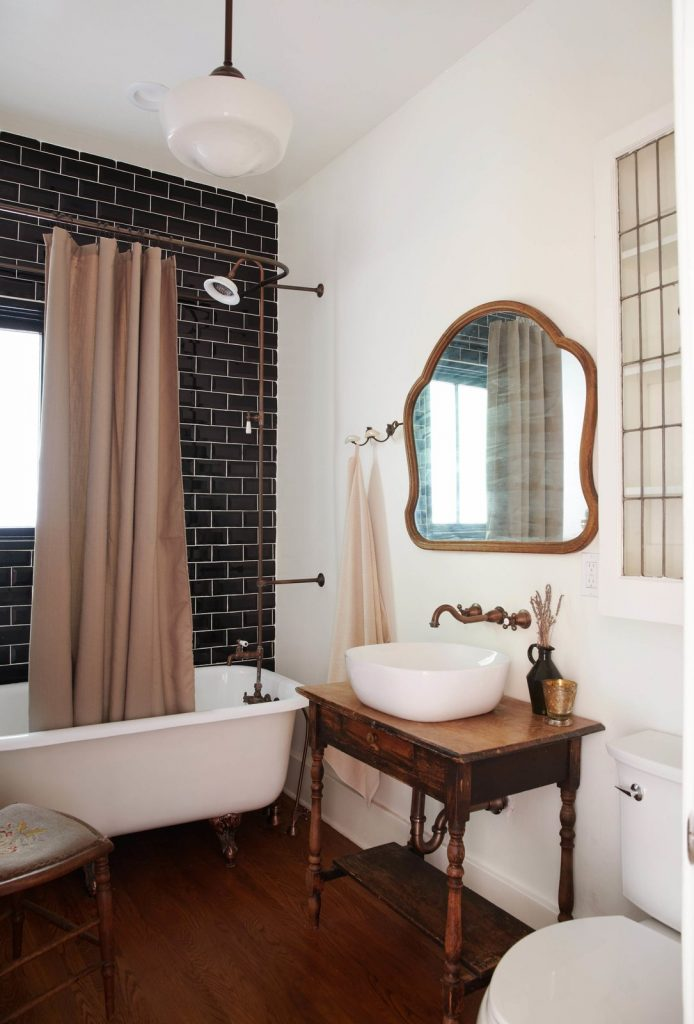 Masculine bathroom with white clawfoot tub, black subway tile and a vessel sink on an antique nightstand.
