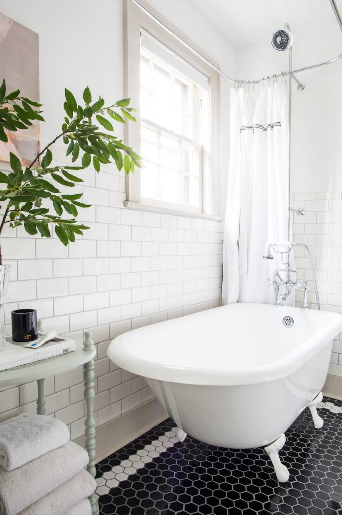 Black and white hex tile floor with white subway tile walls and a white clawfoot tub.