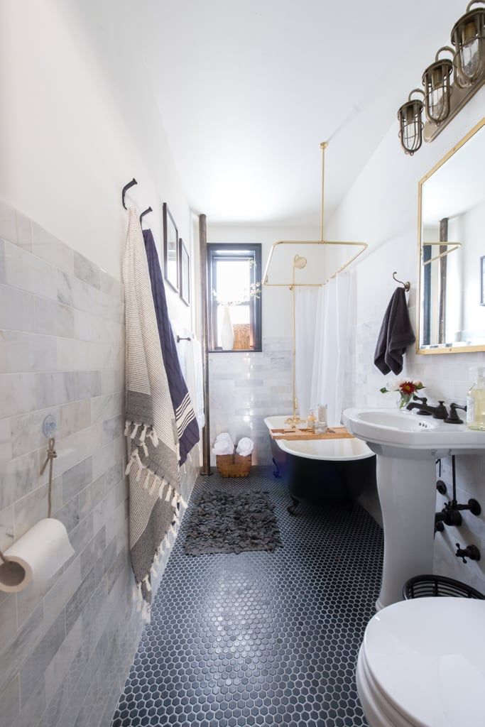 Black clawfoot tub with black penny tile floor, marble walls and brass fixtures.