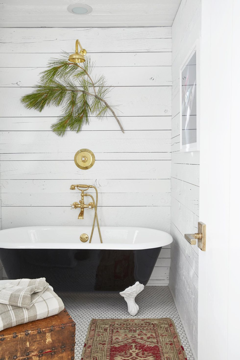 Simple shiplap walls with a back clawfoot tub and brass fixtures.