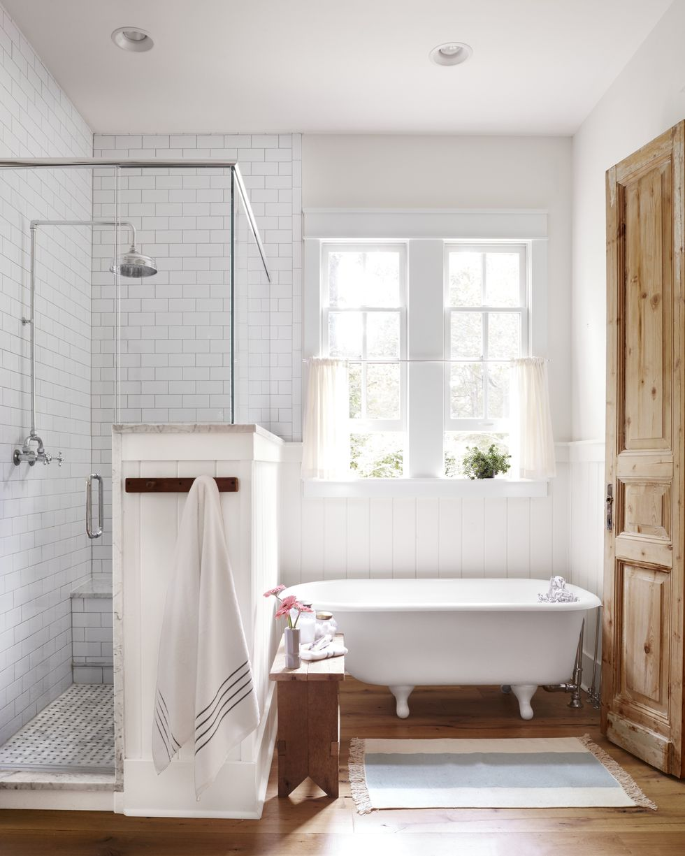 White small clawfoot tub in a bathroom next to a enclosed shower.