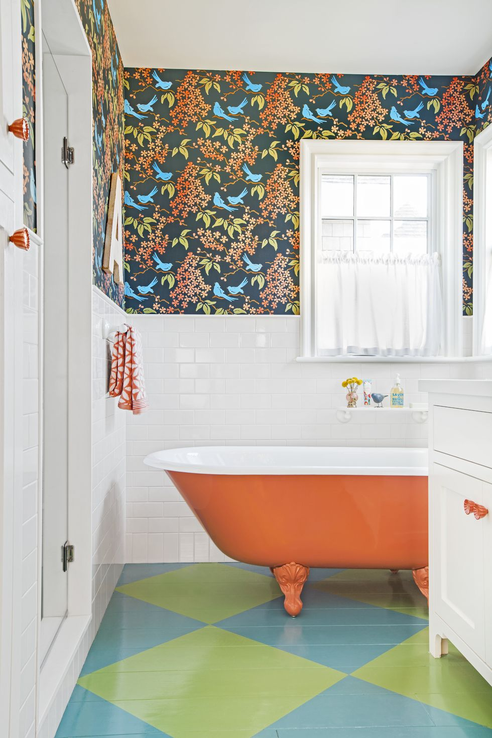 Orange clawfoot tub with painted bathroom floor and colorful wallpaper.