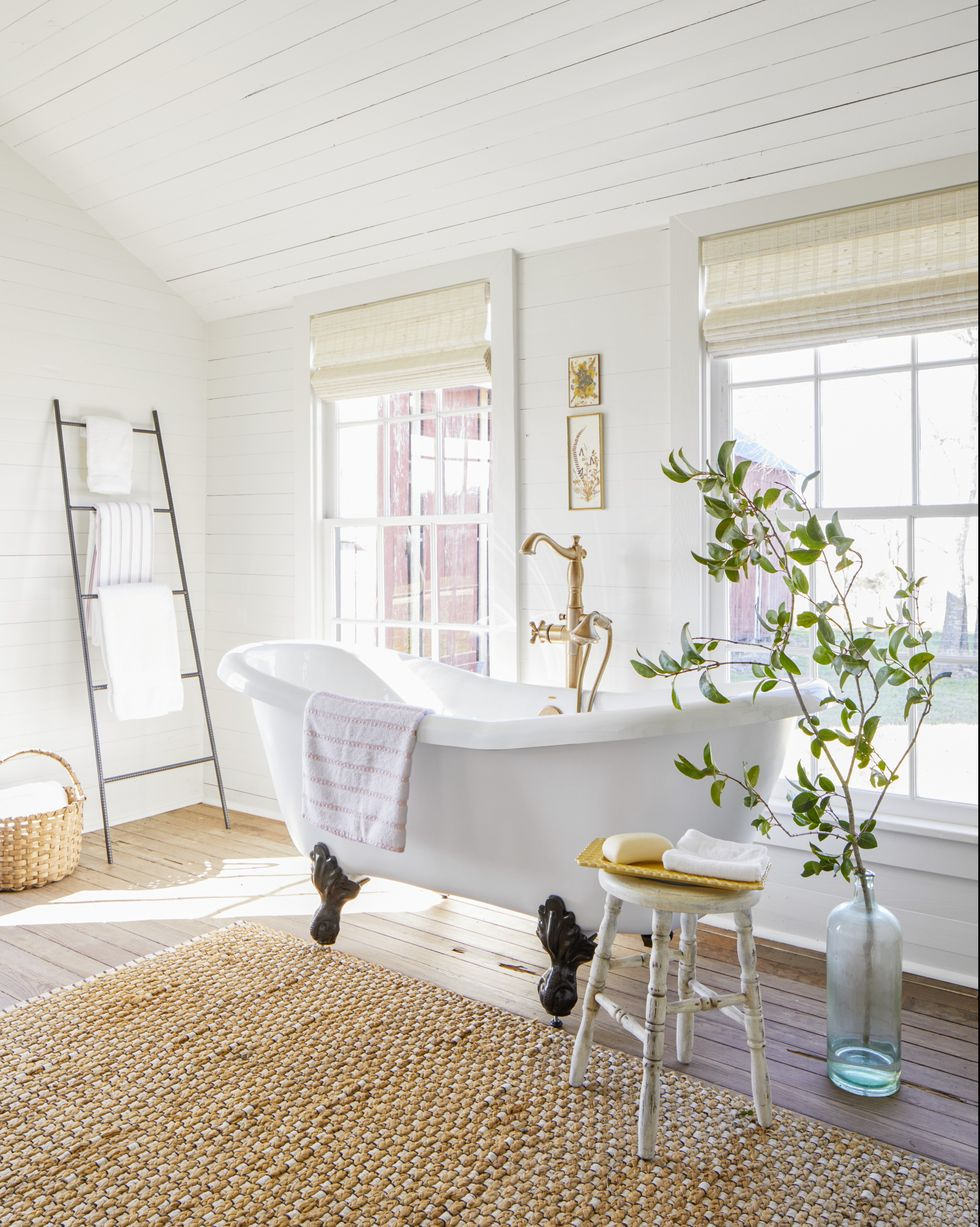 A white clawfoot tub with brass hardware against a shiplap white wall and windows.
