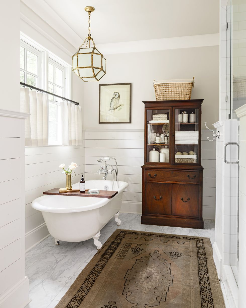white clawfoot tub with shiplap walls. Traditional pendant light and antique cabinet for bathroom storage.