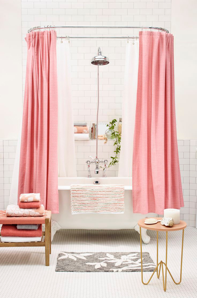 White clawfoot tub with a pink shower curtain in a white bathroom.