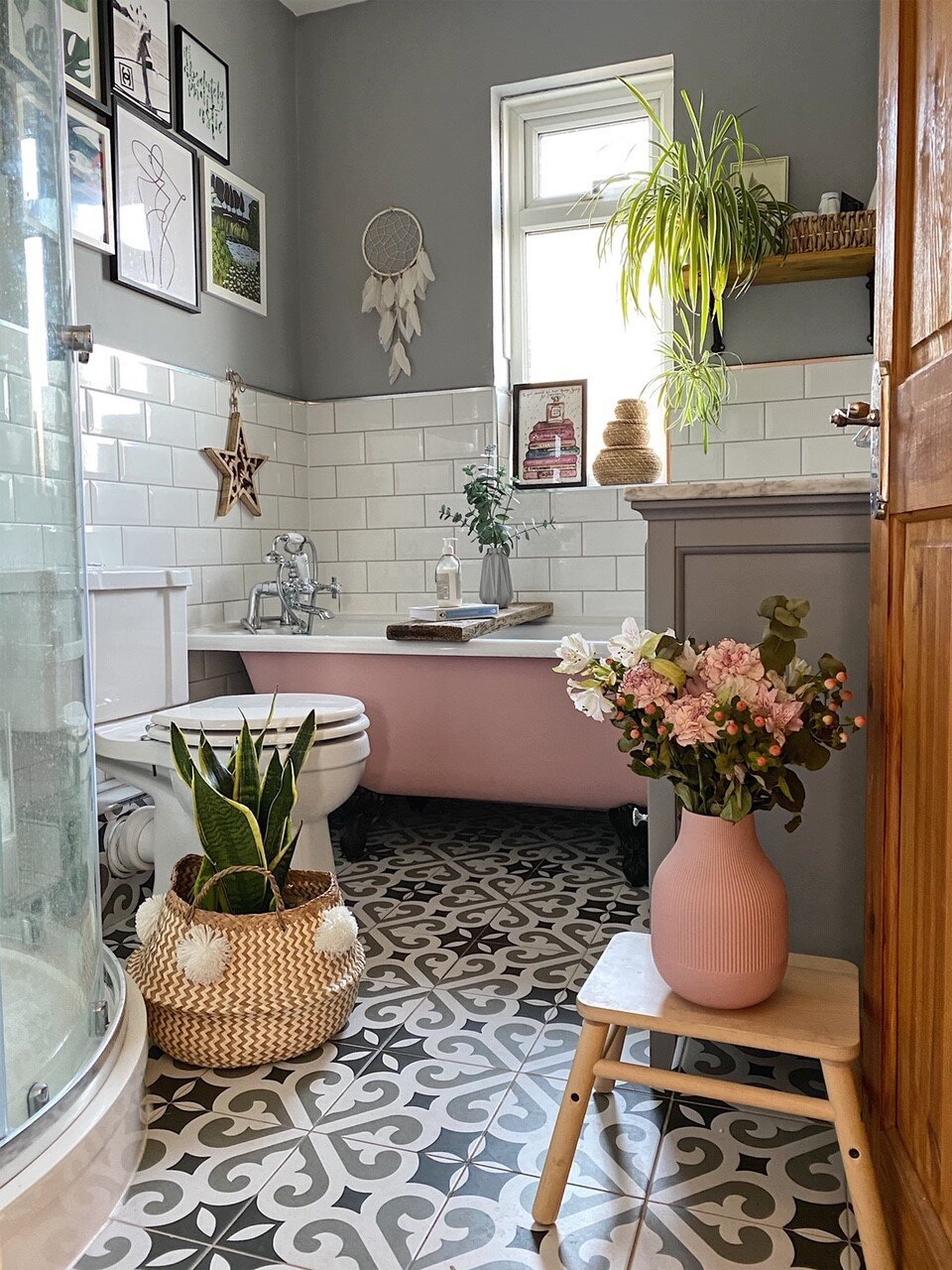 Pink clawfoot tub with modern mosaic tile.