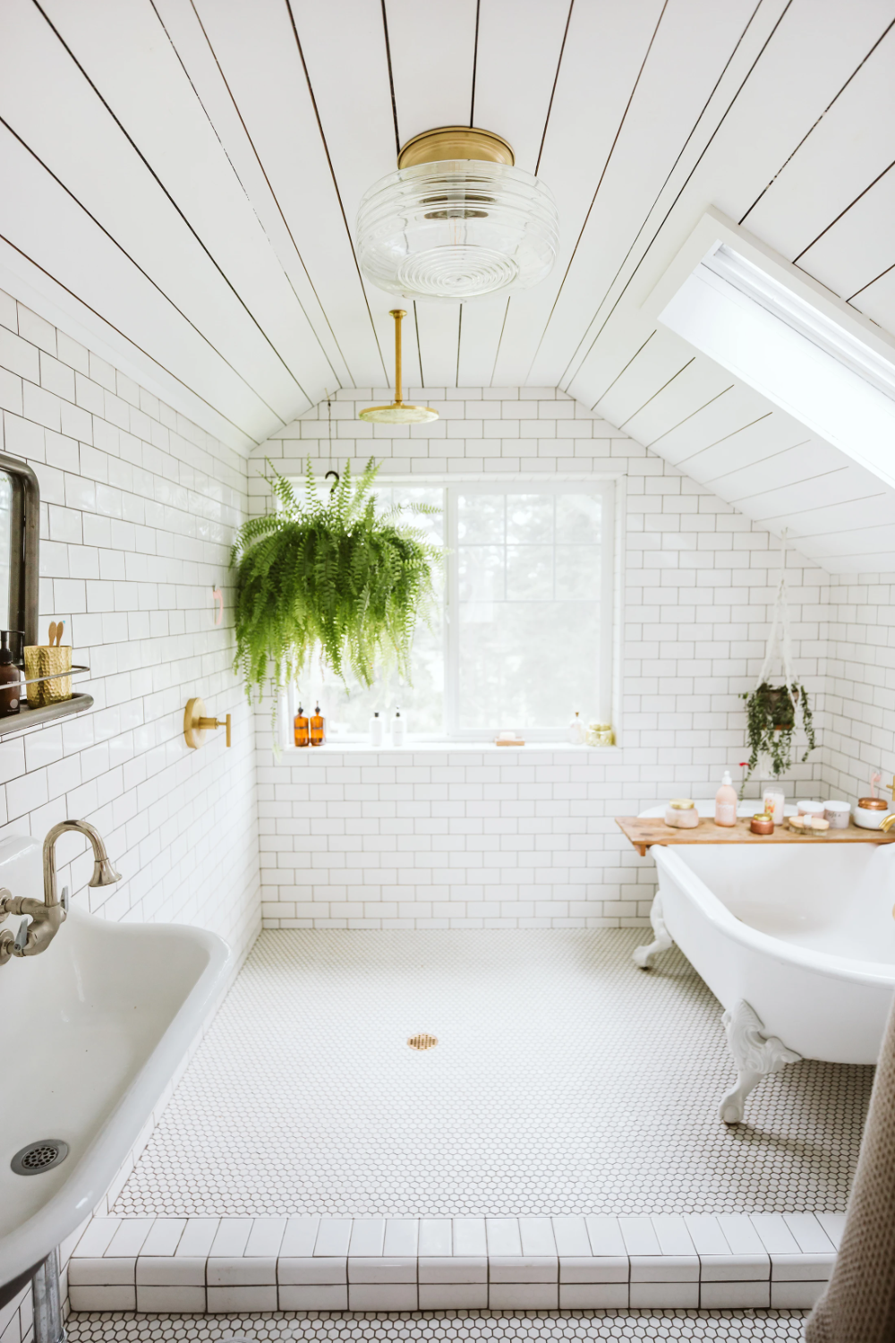 Attic bathroom with subway and penny tile plus white clawfoot tub.