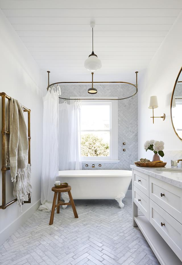 White clawfoot tub with marble herringbone tile walls and floor. Brass hardware