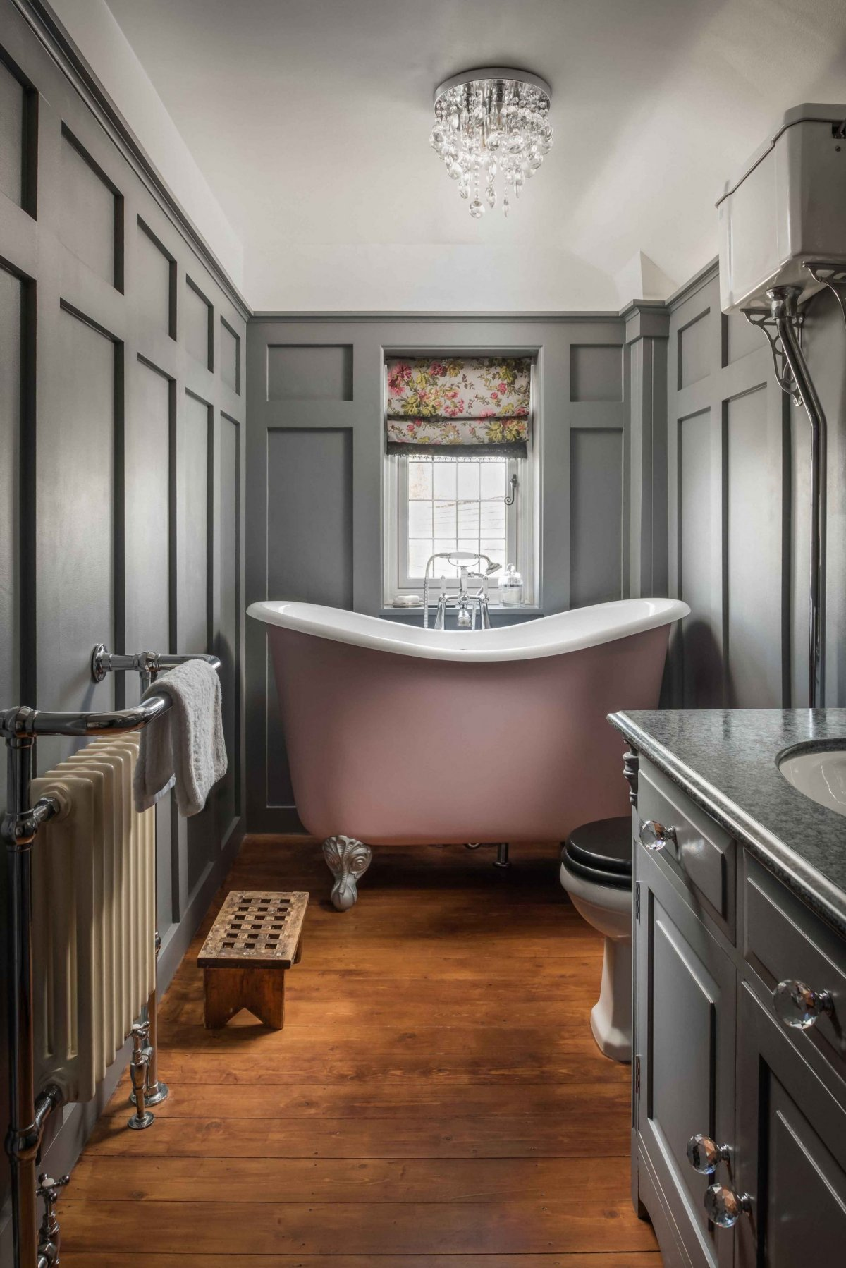 A pink tubby tub which is a higher height and can fit in a small room. Grey wainscoting in a traditional bathroom remodel