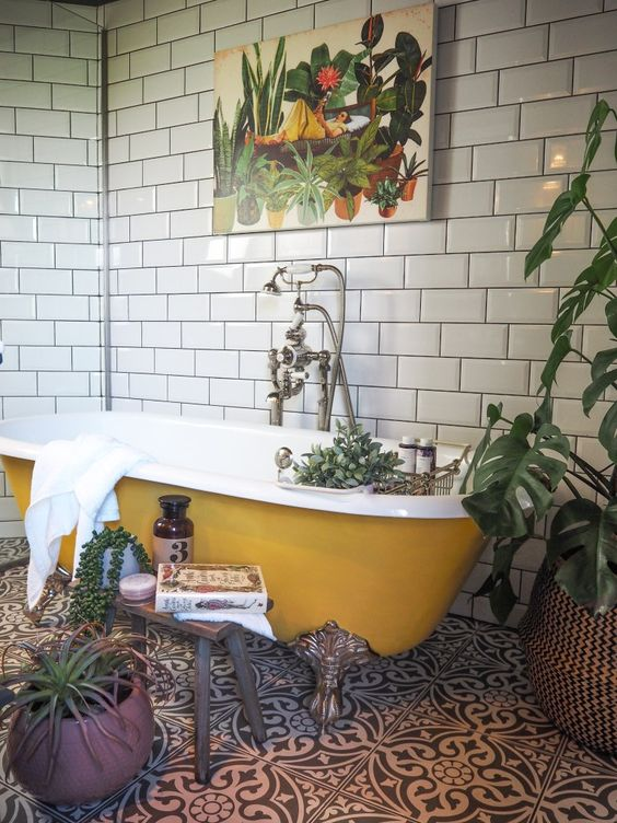 Yellow clawfoot tub with black and white patterned tile in a victorian bathroom remodel