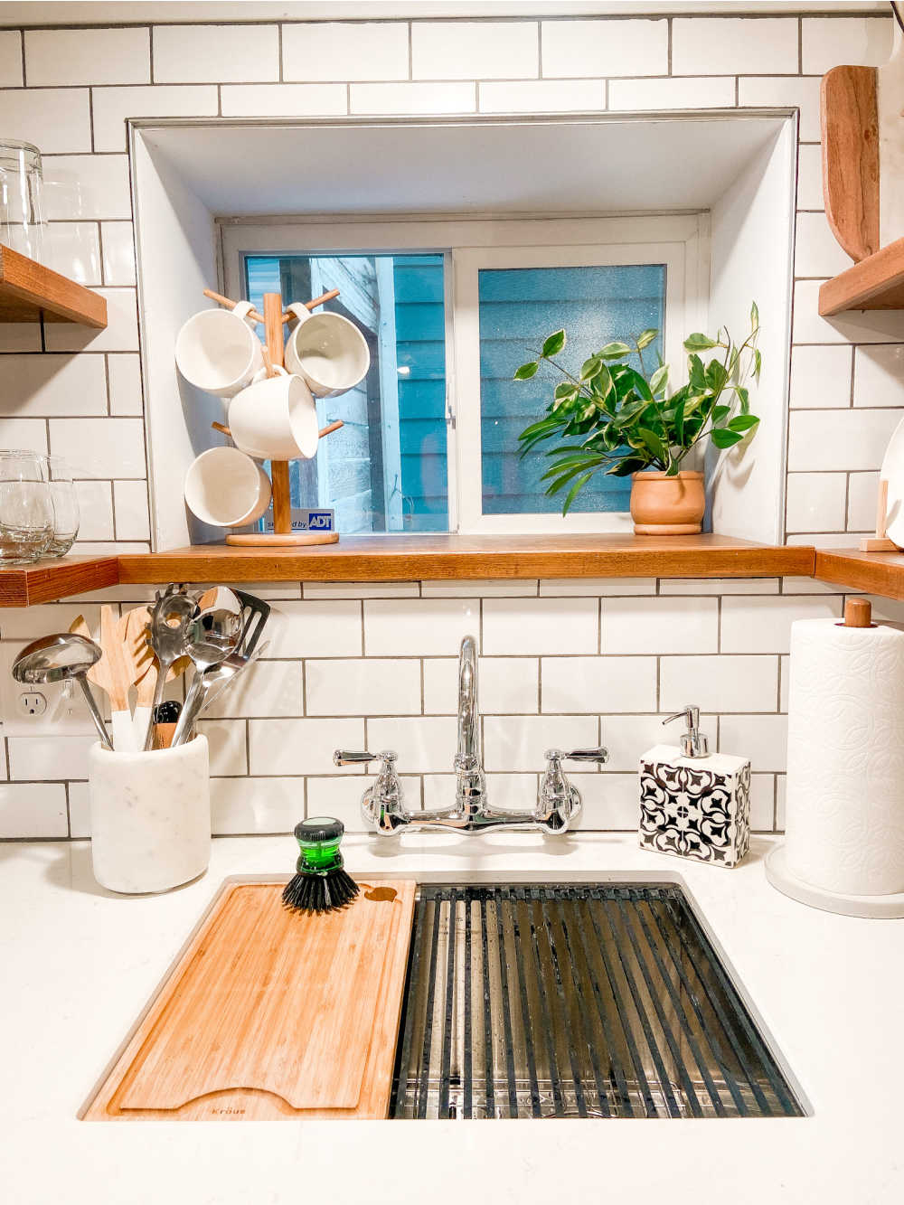 Airbnb kitchen remodel with floating shelves, subway tile and wall-mounted faucet.