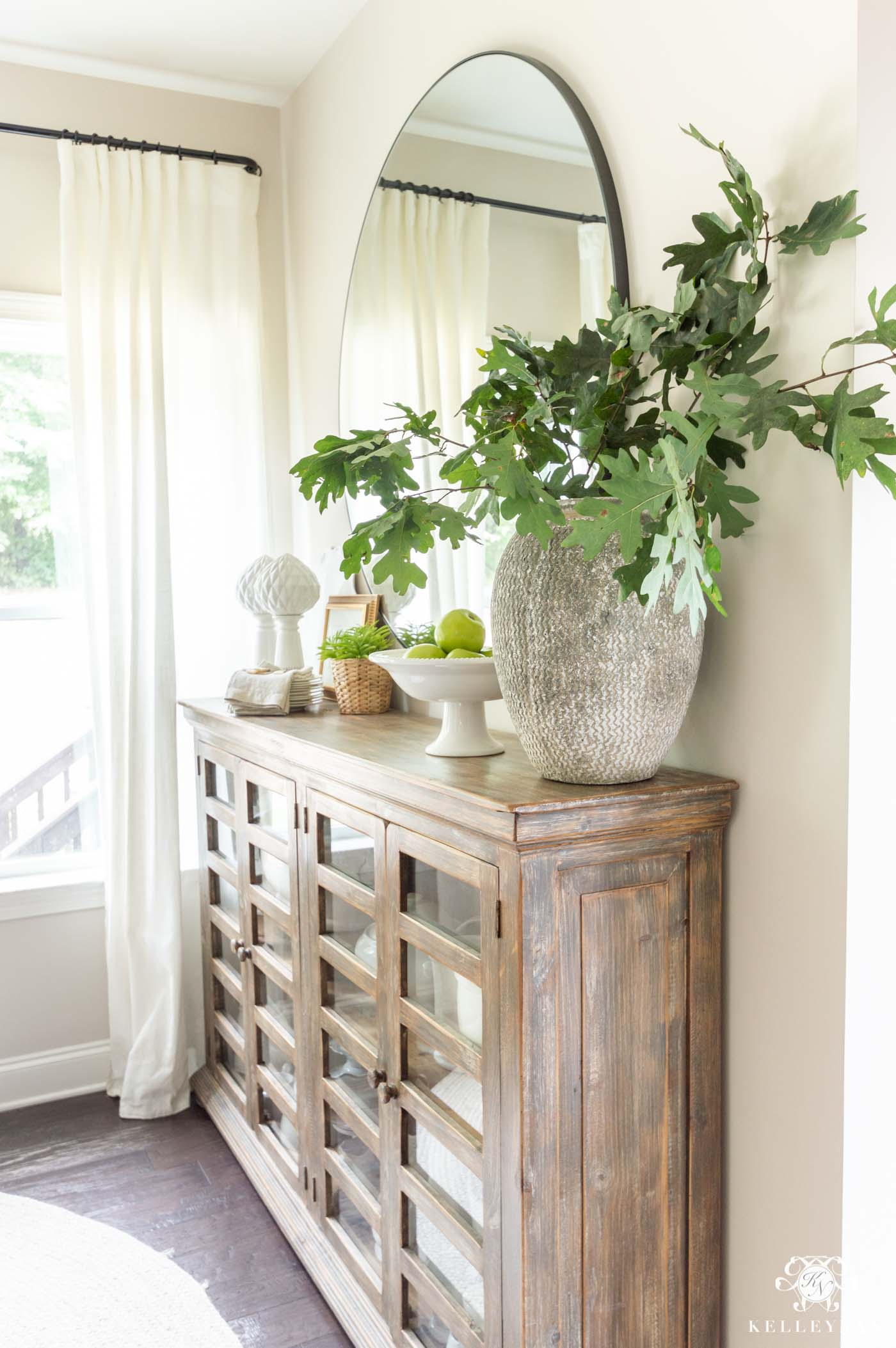 Green oak leaf branches in a tall chippy pottery vase on a dining room console with a footed vessel of green apples and napkins.