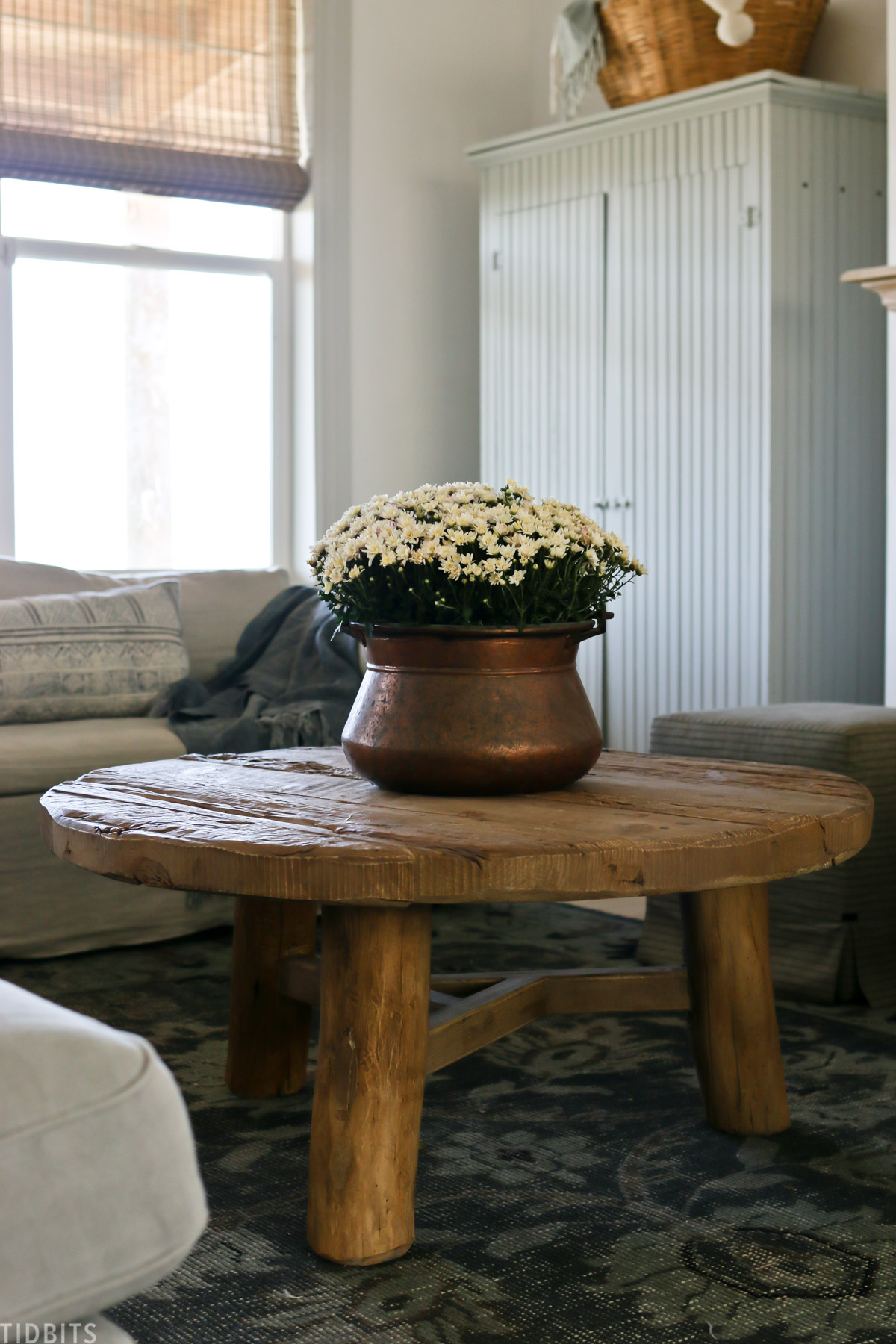 Vintage copper vessel with live mums on a wood coffee table for easy early fall decor.