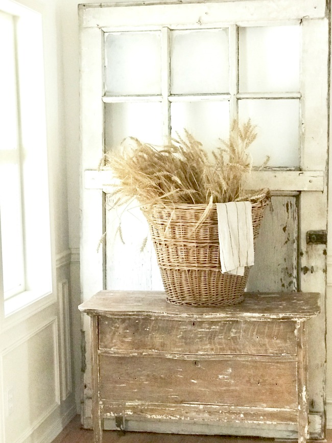 Natural wheat displayed in a vintage basket on a chippy.dresser and a vintage door behind.