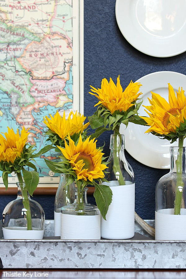 Sunflowers displayed in dipped white vases on a tray from Thistle Key Lane blog.